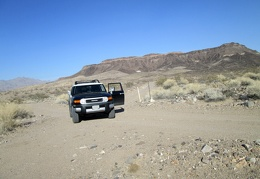 The FJ pauses in front of the short road leading up to an old mining site against the Ship Mountains in the background