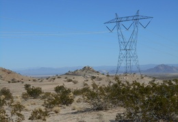 The transmission towers watch over the sandy hills