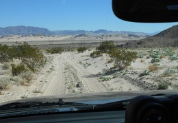 The road descends gently into the far west end of the Devil's Playground area