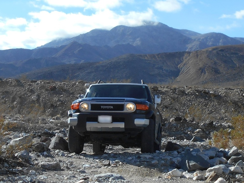 Perfectly positioned between the rocks, I remount the FJ and ride over the hump