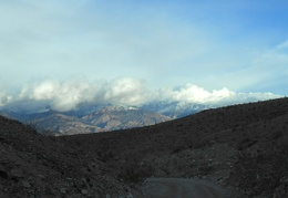 The snow-capped Panamint Mountains peer up above a curve on Minietta Road