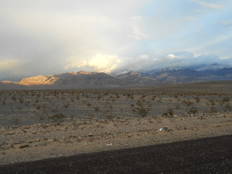 The impending sunset bounces light off a few clouds above the Panamint Mountains