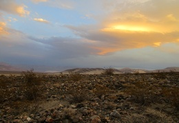 I stop hiking briefly to enjoy the sunset over my rock field and the distant dunes