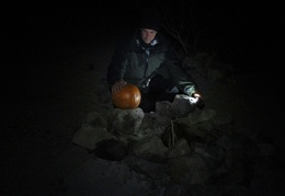 Eric takes a look at a pumpkin found nearby before starting the evening campfire