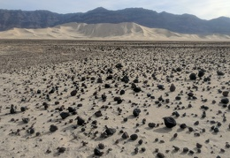Small volcanic rock is scattered across the far shore of Eureka Dry Lake