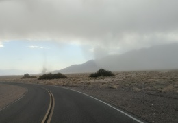 I drive toward a couple of dust devils dancing in front of the Panamint Mountains