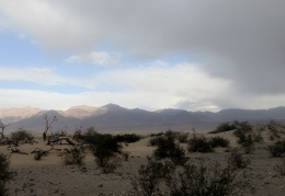 People at Mesquite Dunes are watching the sun hit the Grapevine Mountains