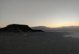 A dark point of Lake Hill sits eerily against the Panamint Dry Lake sunset